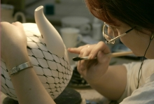 The painter is painting the large tea pot with Cobalt Net pattern